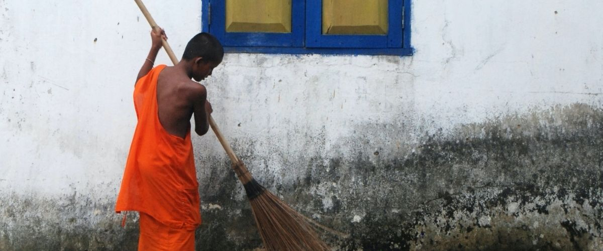 Munk fejer gaden foran sit hjem i Cambodia.